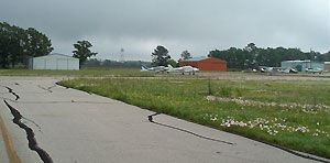 A runway at Muncipal Airport with a plane at the end of it