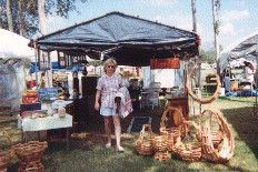 A woman standing in front of a booth at Trade Days with baskets on the ground around her